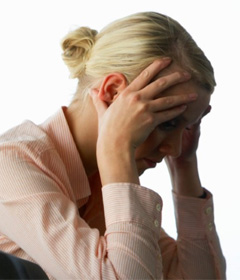 Photo of a woman holding her head as if worried over the risks of independent contractor law